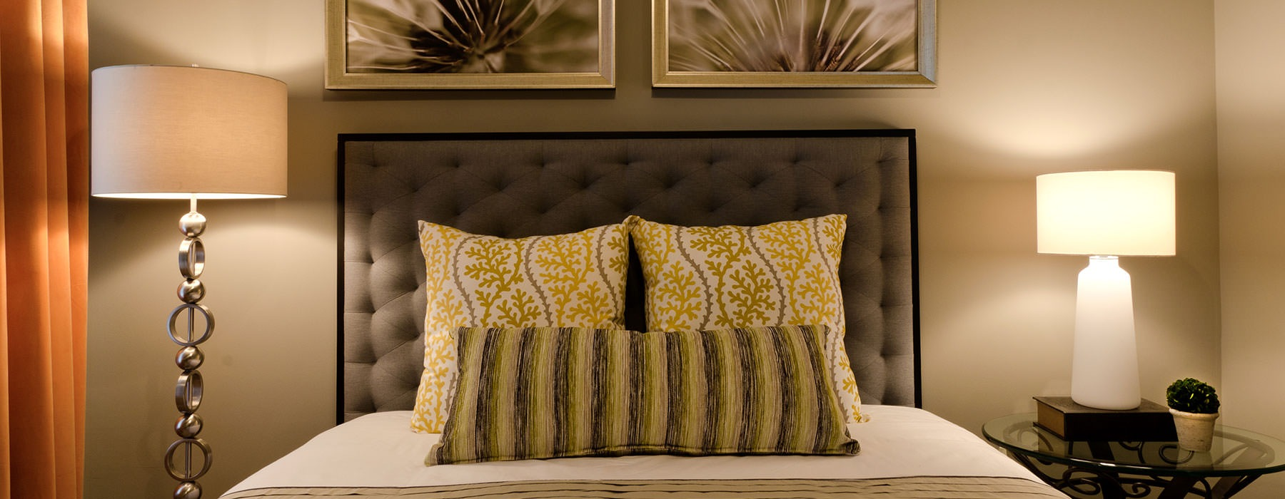 lifestyle image of a bed's headboard, pillow arrangement and lamps