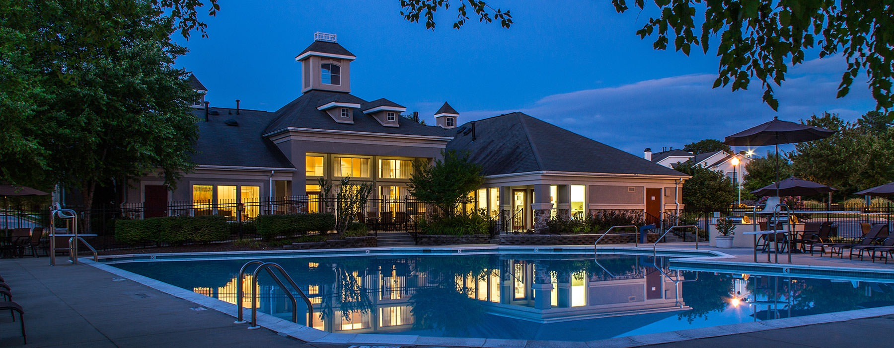 swimming pool at night showing reflection of well-lit property